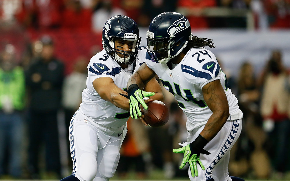 . Russell Wilson #3 hands the ball off to  Marshawn Lynch #24 of the Seattle Seahawks in the second quarter against the Atlanta Falcons during the NFC Divisional Playoff Game at Georgia Dome on January 13, 2013 in Atlanta, Georgia.  (Photo by Kevin C. Cox/Getty Images)