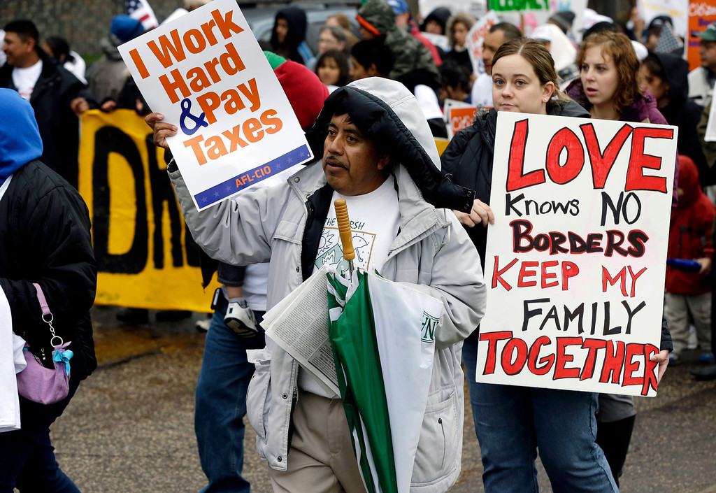 . Demonstrators calling for immigration reform march to the Minnesota State Capitol for a May Day rally Wednesday, May 1, 2013 in St. Paul, Minn. (AP Photo/Jim Mone)