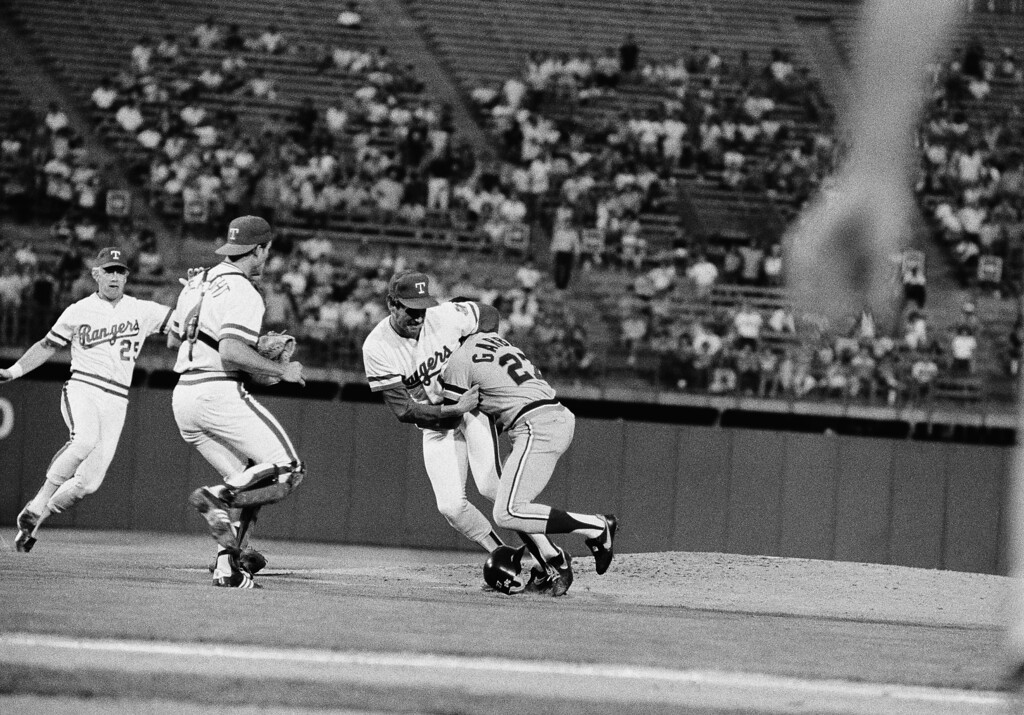 . Detroit Tigers\' first baseman Barbaro Garbey (27) wrestles with Texas Rangers\' pitcher Mike Mason after he was hit by a pitch in the third inning, May 9, 1985 in Arlington, Texas, causing both benches to clear. Detroit won the game 4-1. (AP Photo/Ron Heflin)