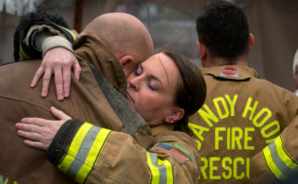 . Sandy Hook Village firefighters embrace after observing a moment of silence near Sandy Hook Elementary on the one week anniversary of the shooting in Newtown, Connecticut December 21, 2012. Many Americans remembered the victims of the Newtown, Connecticut, school massacre with a moment of silence on Friday, as a powerful U.S. gun rights lobbying group prepared to plunge into the national debate over gun control.  REUTERS/Adrees Latif