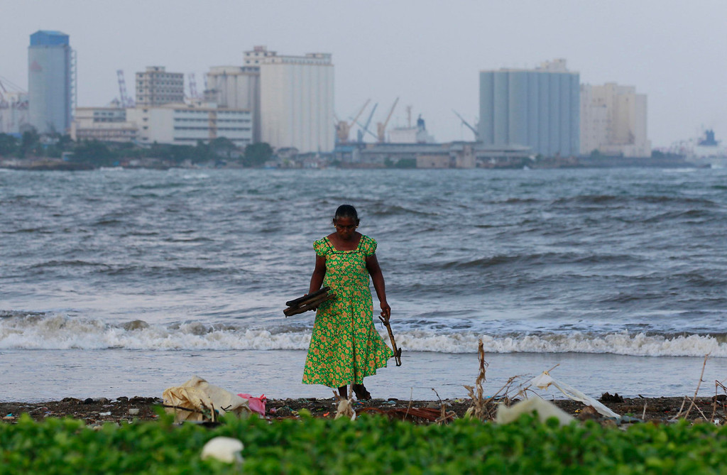 . An elderly Sri Lankan woman collects pieces of wood in the sea promenade of Colombo port, in Colombo, Sri Lanka, Wednesday, Oct. 2, 2013. The world is aging so fast that most countries are not prepared to support their swelling numbers of elderly people, according to a global study being issued Tuesday by the United Nations and an elder rights group. (AP Photo/Eranga Jayawardena)