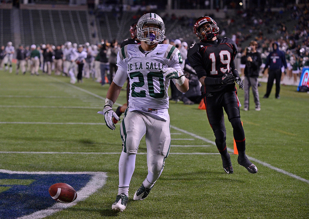 . De La Salle Spartans\' Tiapepe Vitale (20) scores with a 46-yard touchdown run as Centennial Huskies\' Gavin Andrews (19) stands dejected in the second quarter of the Open Division during the 2012 CIF State Football Championship at Home Depot Center in Carson, Calif. on Saturday, Dec. 15, 2012. (Jose Carlos Fajardo/Staff)