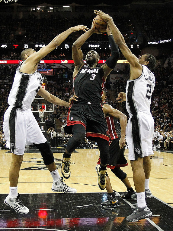 . Miami Heat\'s Dwyane Wade (3) is defended by San Antonio Spurs\' Tim Duncan, left, and Kawhi Leonard (2) during the first half at Game 5 of the NBA Finals basketball series, Sunday, June 16, 2013, in San Antonio. (AP Photo/Mike Stone, Pool)