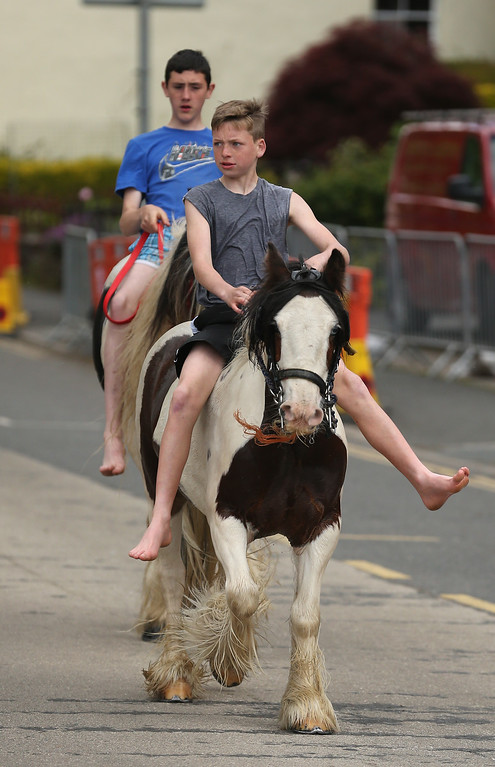 . Young travelers parade their horses through Appleby during the Appleby Horse Fair on June 4, 2015 in Appleby, England. The Appleby Horse Fair has existed under the protection of a charter granted by James II since 1685 and is one of the key gathering points for the Romany, gypsy and traveling community. The fair is attended by about 5,000 travelers who come to buy and sell horses. The animals are washed and groomed before being ridden at high speed along the \'mad mile\' for the viewing of potential buyers.  (Photo by Christopher Furlong/Getty Images)