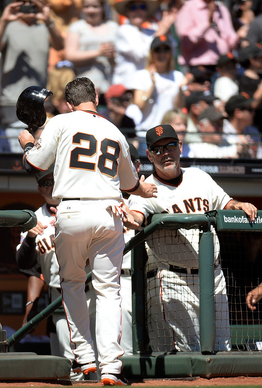 . Buster Posey #28 of the San Francisco Giants is congratulated by manager Bruce Bochy #15 after Posey scored against the Colorado Rockie in the bottom of the second inning at AT&T Park on April 10, 2013 in San Francisco, California.  (Photo by Thearon W. Henderson/Getty Images)
