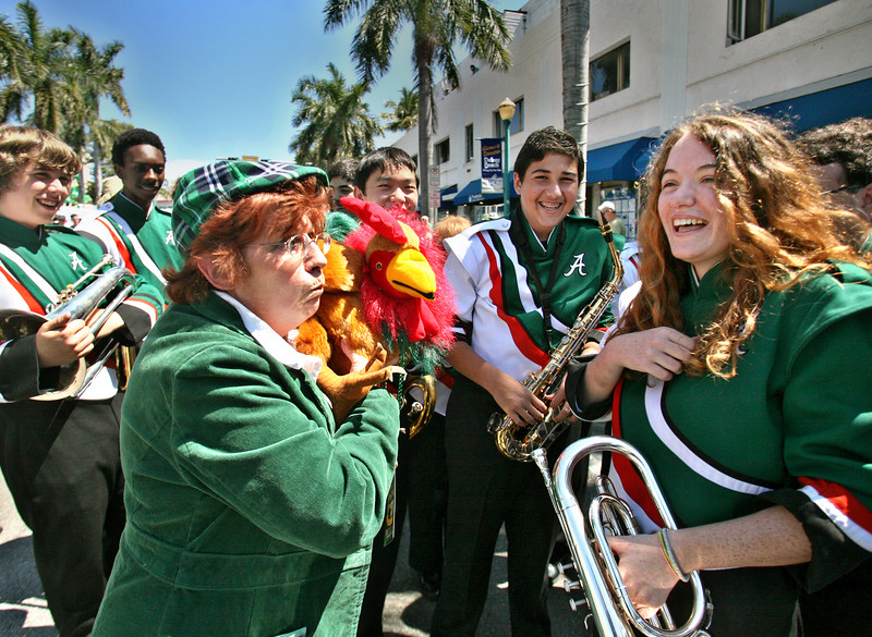 031613 - DELRAY BEACH - Sue Simon and her puppet Cluck O'Shea entertain some of the members of The Atlantic War Eagle Marching Band before the start of the 45th Annual Delray Beach St. Patrick's Day Parade. Sue Simon and her puppet Cluck O'Shea marched in the parade and were representing the Puppet Arts Center in Delray.   Photo by Tim Stepien
