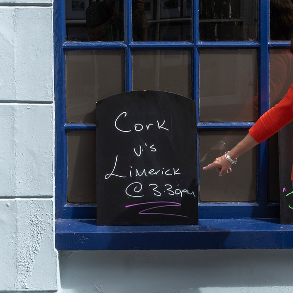 Woman pointing out time of sport event against pub window, Kinsale, County Cork, Ireland