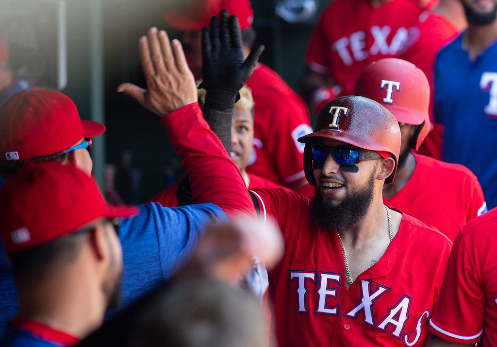 . Texas Rangers\' Rougned Odor (12) celebrates with teammates after hitting a solo home run during the eighth inning of a baseball game against the Cleveland Indians, Sunday, July 22, 2018, in Arlington, Texas. (AP Photo/Sam Hodde)