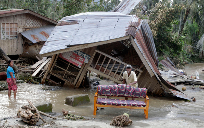 . Residents clean their sofa outside their destroyed house after Typhoon Bopha hit Compostela Valley, southern Philippines December 5, 2012. Blocked roads and severed communications in the southern Philippines frustrated rescuers on Wednesday as teams searched for hundreds of people missing after the strongest typhoon this year killed at least 283 people. REUTERS/Erik De Castro