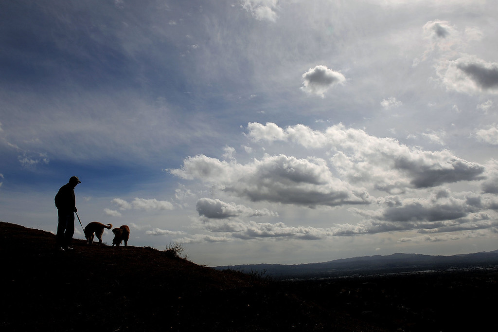 """. Clouds hover over the San Fernando Valley as John Nicsinger walks his dogs \""""Dandy\"""" and \""""Bailey\"""" at Palisades Park in Porter Ranch, CA February 27, 2014.(Andy Holzman/Los Angeles Daily News)"""