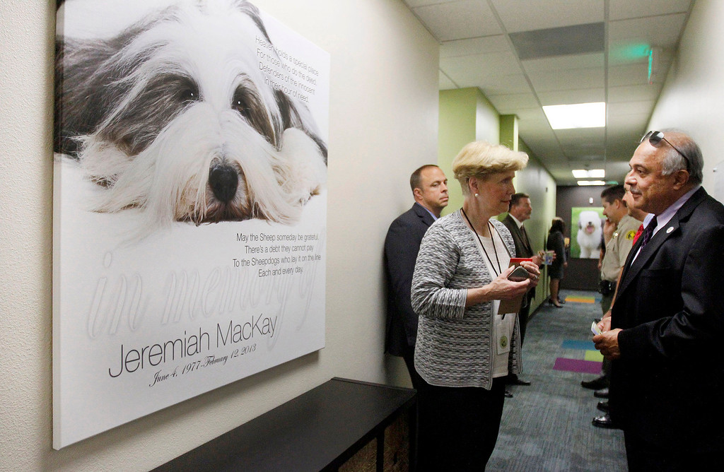 . David Hidalgo, right, Supervising District Attorney for the Rancho Cucamonga Criminal Division, chats with Marie Dawson, of the Children\'s Assessment Center, as they stand next to a large canvas photo created in memory of slain San Bernardino County Sheriff\'s Deputy Jeremiah MacKay, for whom a wing of the center was dedicated on Wednesday, May 21, 2014 at the Children\'s Assessment Center in San Bernardino, Ca. (Photo by Micah Escamilla/San Bernardino Sun)