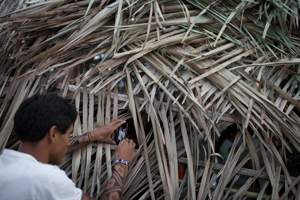 . A man uses a phone to make a picture of those inside a traditional indigenous home during the indigenous games in Cuiaba, Brazil, Tuesday, Nov. 12, 2013.  (AP Photo/Felipe Dana)