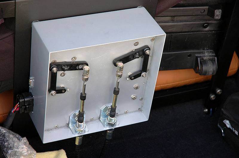 In the boot, held by a couple of brackets, the shifting mechanism was demonstrated with the cover removed. With the car off, the owner clicked the paddle shifters (once per shift position) then engaged the clutch. At that point, the computer-controlled electric-powered shift mechanism sprang to life and shifted very quickly (milliseconds) into the desired gear. No short shifter required.