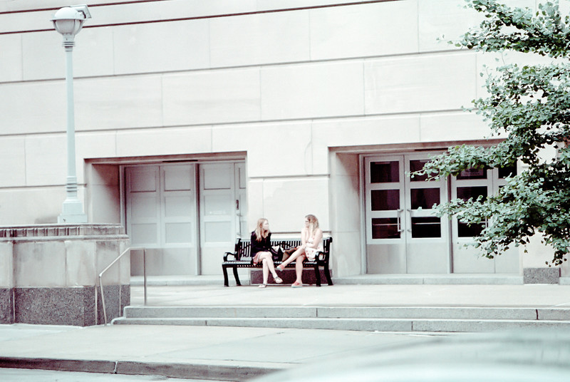 A conversation on a bench across the street