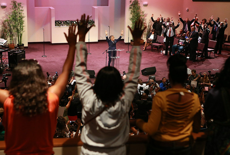 . The Rev. Al Sharpton raises his hands with the crowd during a service for the Michael Brown family at the Greater Grace Church in Ferguson, Mo. on Sunday, Aug. 17, 2014. On Saturday, Aug. 9, 2014, a white police officer fatally shot Brown, an unarmed black teenager, in the St. Louis suburb. (AP Photo/St. Louis Post-Dispatch, Christian Gooden)