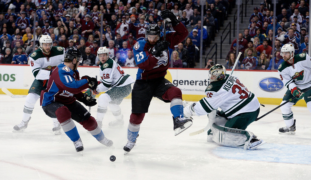 . Colorado Avalanche left wing Jamie McGinn (11) and Colorado Avalanche center Maxime Talbot (25) keep the puck in the zone as Minnesota Wild goalie Darcy Kuemper (35) eyes the play during the first period.  (Photo by John Leyba/The Denver Post)