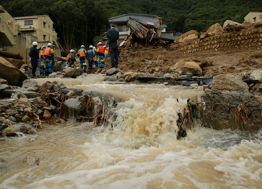 . Members of police continue the search for missing people among the debris of houses destroyed by a landslide caused by torrential rain at the site of a landslide in a residential area on August 20, 2014 in Hiroshima, Japan.  (Photo by Buddhika Weerasinghe/Getty Images)