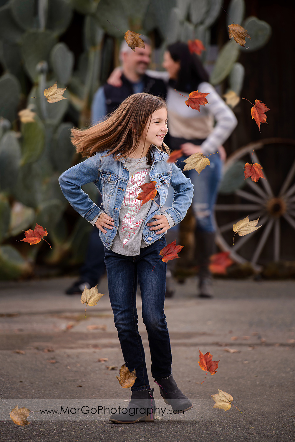 young girl dancing with falling leaves with parents looking at each other in the background during family session at Old Borges Ranch in Walnut Creek