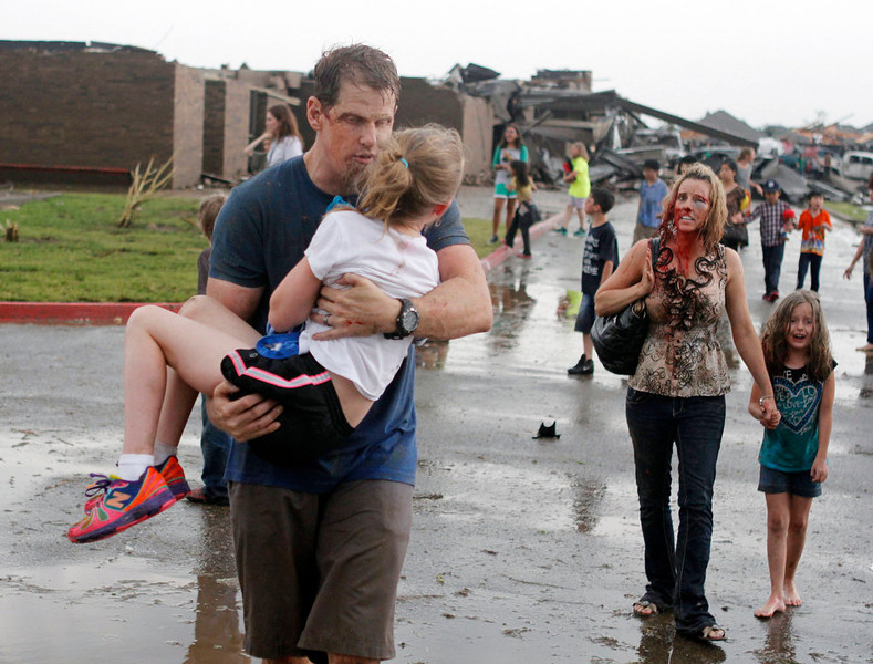 . Teachers carry children away from Briarwood Elementary school after a tornado destroyed the school in south Oklahoma City, Monday, May 20, 2013. A monstrous tornado roared through the Oklahoma City suburbs, flattening entire neighborhoods with winds up to 200 mph, setting buildings on fire and landing a direct blow on an elementary school. (AP Photo/The Oklahoman, Paul Hellstern)