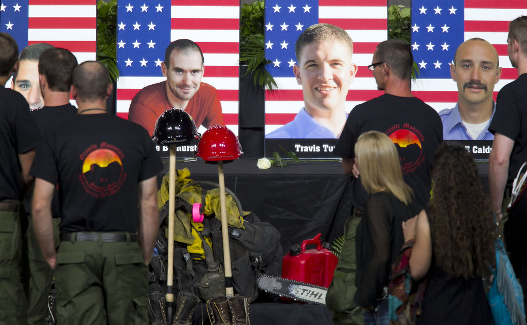 . Photos of some of the 19 fallen firefighters line the front of the stage before a memorial service at Tim\'s Toyota Center July 9, 2013 in Prescott Valley, Arizona. (Photo by  David Wallace-Pool/Getty Images)