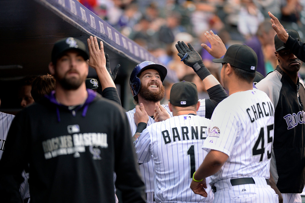 . DENVER, CO - MAY 06: Colorado Rockies center fielder Charlie Blackmon (19) gets his beard pulled by Colorado Rockies right fielder Brandon Barnes (1) in the dug out after hitting a home run off of Texas Rangers starting pitcher Robbie Ross (46) in the first inning May 6, 2014 at Coors Field. (Photo by John Leyba/The Denver Post)
