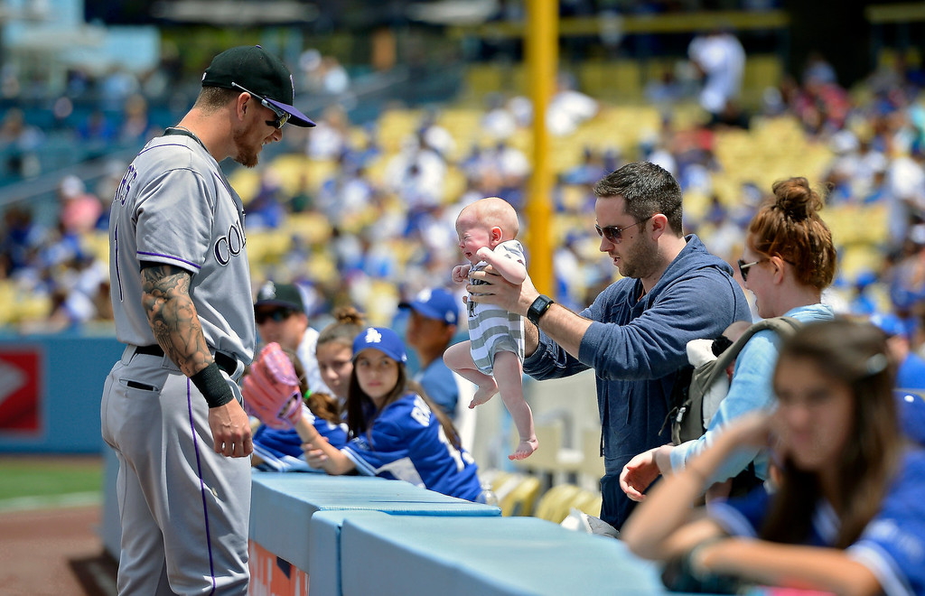 . Colorado Rockies\' Brandon Barnes, left, greets his nephew Declan Dooley, center, as his brother-in-law Carey Dooley holds him up before a baseball game against the Los Angeles Dodgers, Sunday, April 27, 2014, in Los Angeles. (AP Photo/Mark J. Terrill)
