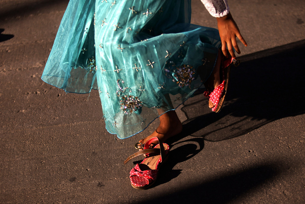 . A Muslim girl puts her sandals on after the Eid al-Fitr dawn prayer at Lisbon\'s Martim Moniz square, Thursday, Aug. 8, 2013. Eid al-Fitr, one of the most important holidays in the Muslim world, marks the end of the holy fasting month of Ramadan and is celebrated with prayers and family reunions. (AP Photo/Francisco Seco)