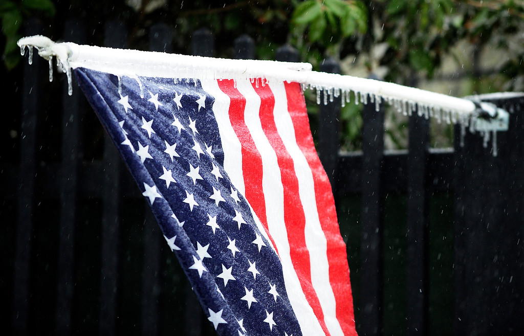 . Ice forms on a U.S. flag and it\'s pole at a home off Lombardy Court Wednesday, Feb. 12, 2014, in Augusta, Ga. Sleet, ice and fallen trees prevelent in the Hill area near Highland Avenue and Lombardy Court as a winter storm hits the Augusta area  (AP Photo/The Augusta Chronicle, Sara Caldwell)