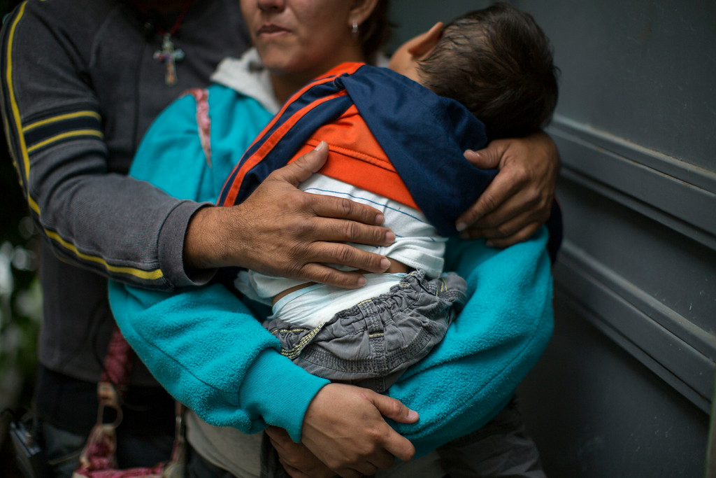 . In this June 19, 2014 photo, a Honduran man hugs his wife as she carries their son, at a immigrant shelter in Guatemala City. They wait in Guatemala before continuing their trip North to the United States. The belief that women and children can safely surrender to authorities the moment they set foot in the U.S. has changed the calculus of tens of thousands of parents who no longer worry about their children finishing the dangerous trip north through Mexico with a potentially deadly multiday hike through the desert Southwest. (AP Photo/Luis Soto)