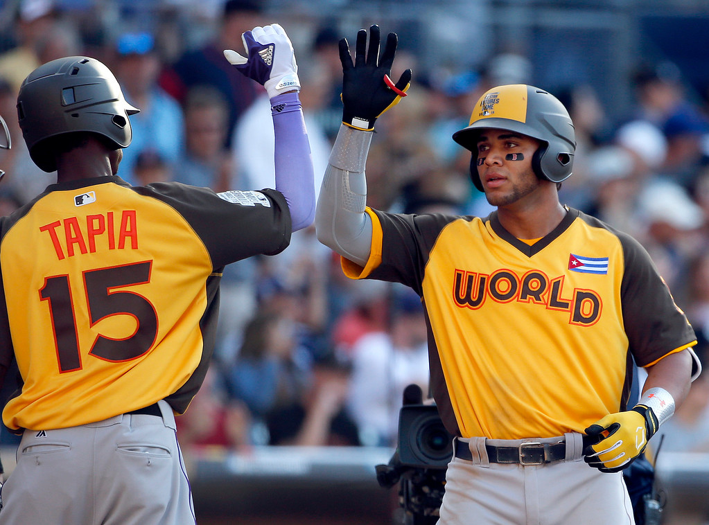. World Team\'s Yoan Moncada, of the Boston Red Sox, greets teammate Raimel Tapia, of the Colorado Rockies (15), after hitting a two-run home run against the U.S. Team during the eighth inning of the All-Star Futures baseball game, Sunday, July 10, 2016, in San Diego. (AP Photo/Lenny Ignelzi)
