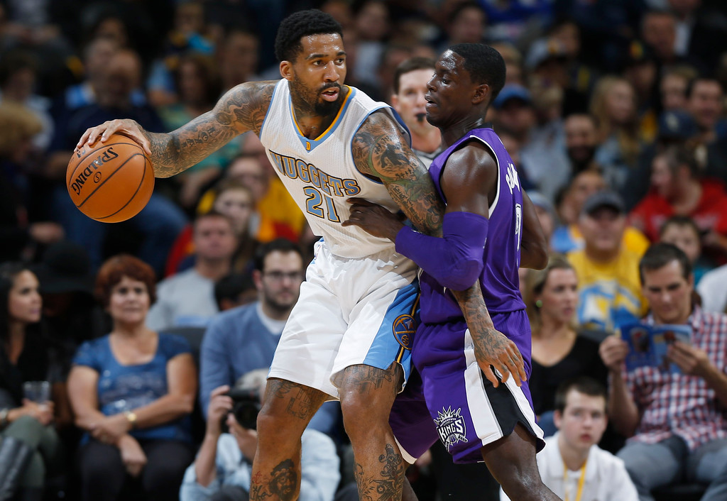 . Denver Nuggets forward Wilson Chandler, left, works the ball inside for shot as Sacramento Kings guard Darren Collison covers in the first half of an NBA basketball game in Denver on Monday, Nov. 3, 2014. (AP Photo/David Zalubowski)