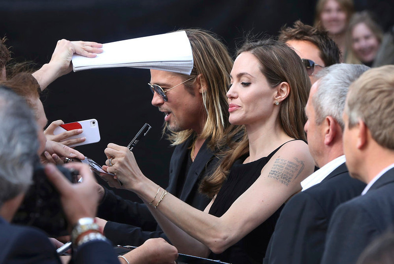 . Angelina Jolie signs autographs with her husband Brad Pitt as they arrive for the world premiere of his film World War Z in London June 2, 2013.   REUTERS/Neil Hall