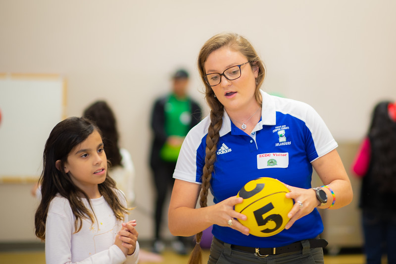 Amanda Geary gives instruction to elementary students on how to properly pass a ball.