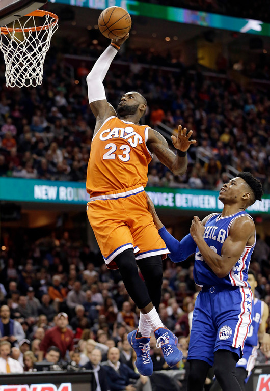 . Cleveland Cavaliers\' LeBron James, left, dunks the ball against Philadelphia 76ers\' Richaun Holmes in the first half of an NBA basketball game, Friday, March 31, 2017, in Cleveland. (AP Photo/Tony Dejak)
