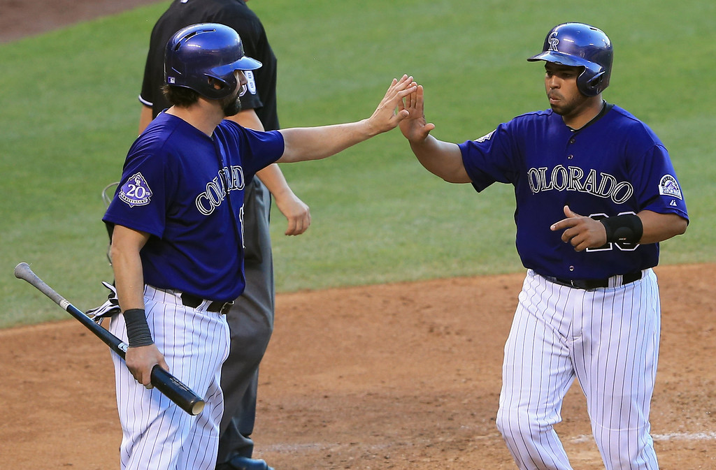 . DENVER, CO - JULY 26:  Todd Helton #17 of the Colorado Rockies and Wilin Rosario #20 of the Colorado Rockies celebrate after scoring on a double by Tyler Chatwood #32 of the Colorado Rockies off of Wily Peralta #60 of the Milwaukee Brewers in the second inning at Coors Field on July 26, 2013 in Denver, Colorado.  (Photo by Doug Pensinger/Getty Images)