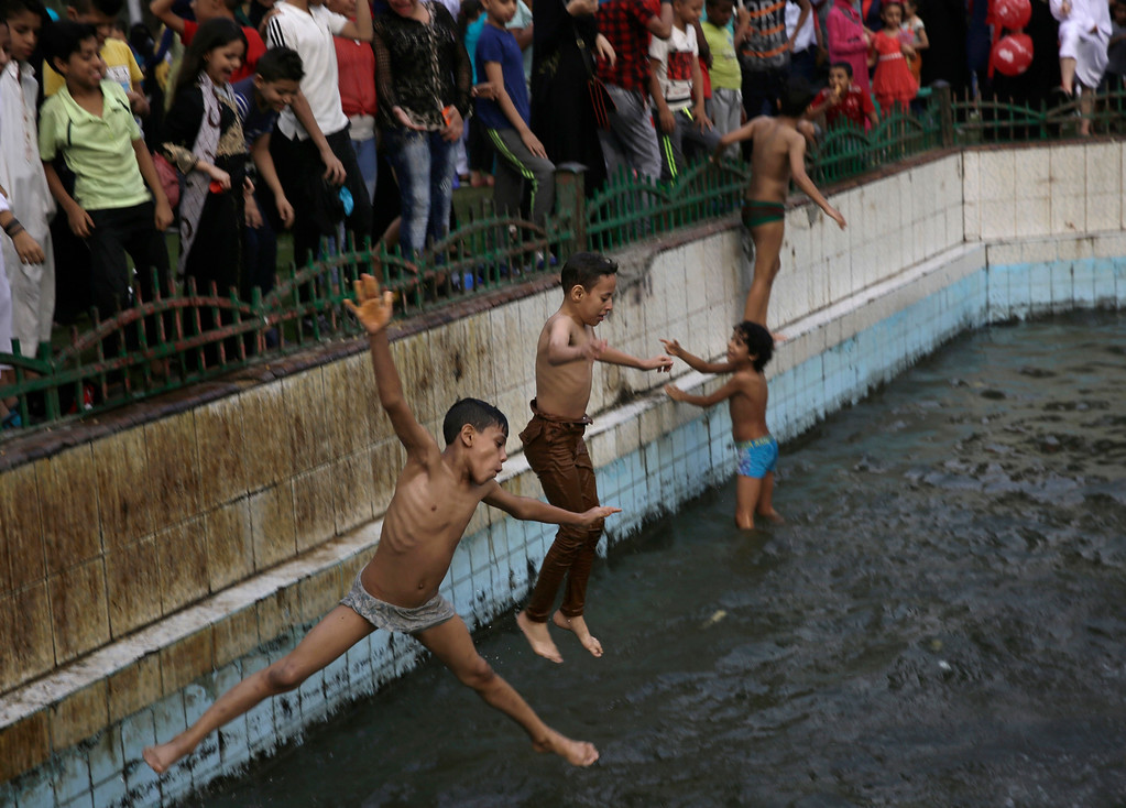 . Boys swim in a public fountain after the dawn Eid al-Adha prayers at Moustafa Mahmoud Square in Cairo, Egypt, Monday, Sept. 12, 2016. (AP Photo/Thomas Hartwell)