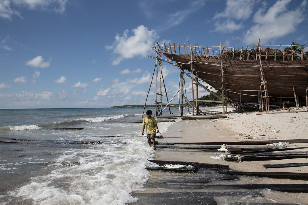 . A Buginese man holds a rope as he prepare to pull a wooden block with his friend at Tanjung Bira Beach on May 2, 2014 in Bulukumba, South Sulawesi, Indonesia.  (Photo by Agung Parameswara/Getty Images)