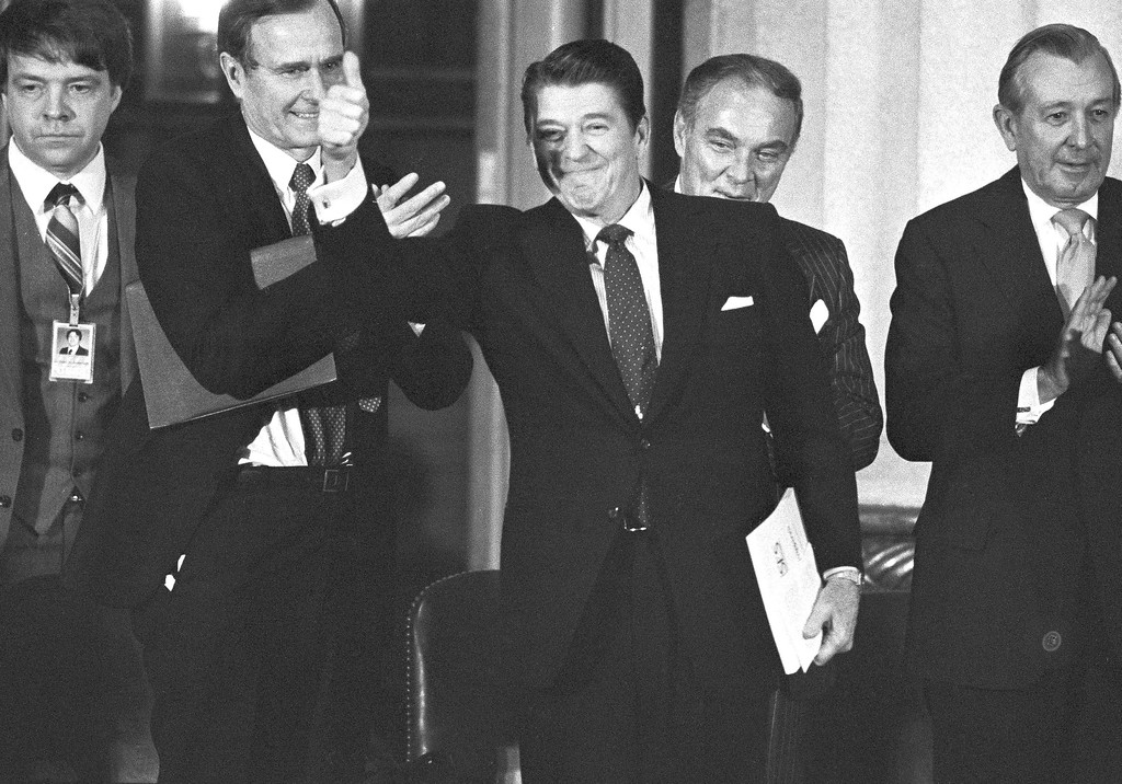 """. President Ronald Reagan gives the thumbs up sign after giving a speech to the Reagan Administration Executive Forum in Washington, Jan. 20, 1982, on the anniversary of his first year in office. In his speech, Reagan told the government\'s top 2,200 officials that \""""we have laid the foundations for economic recovery and national renewal.\"""" Vice President George Bush, left, and Secretary of State Alexander Haig, right, applaud the president. (AP Photo/Jeff Taylor)"""