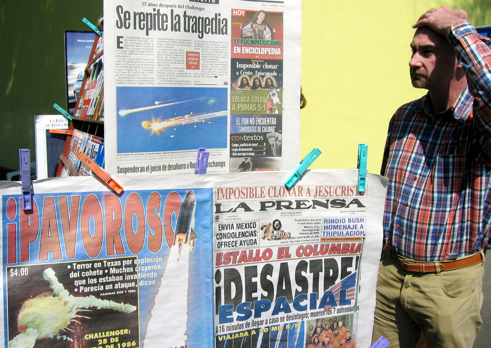 . A pedestrian in Mexico City reads the headlines of local newspapers Sunday Feb. 2, 2003, the day after the space shuttle Columbia broke up over Texas, killing all seven astronauts on board.(AP Photo/Jose Luis Magana)