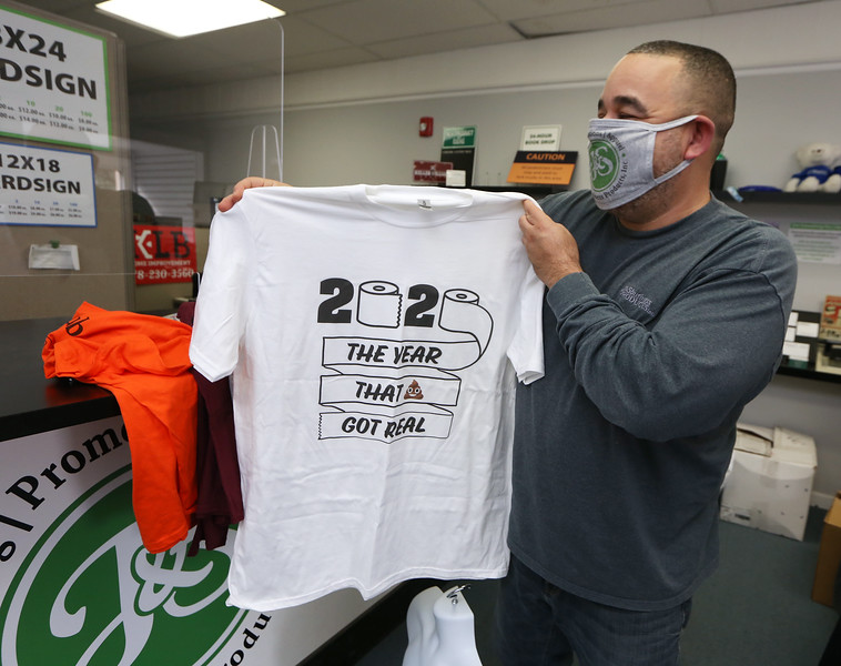 Jose Banchs of Shirley, owner of J & S Business Products, shows some of the tee shirts he's making during the pandemic. (SUN/Julia Malakie)