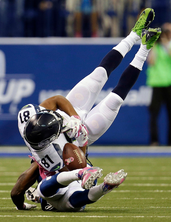 . Seattle Seahawks wide receiver Golden Tate, top, loses control of the ball as he flips over Indianapolis Colts cornerback Greg Toler during the second half of an NFL football game in Indianapolis, Sunday, Oct. 6, 2013. The pass was incomplete. The Colts defeated the Seahawks 34-28. (AP Photo/AJ Mast)