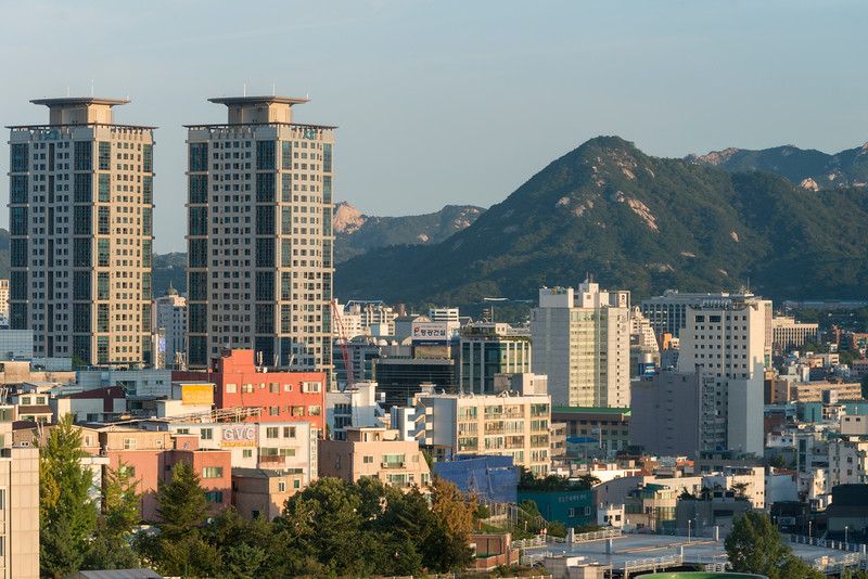 Buildings in city with mountain in background, Seoul, South Korea