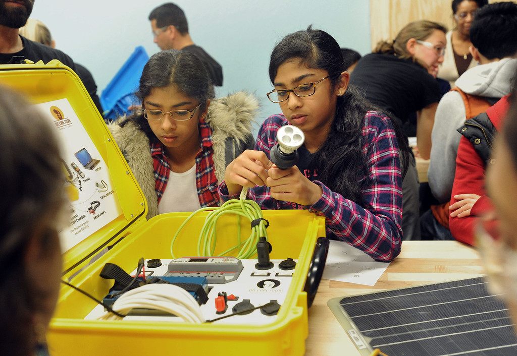 . Anita Ilango, 13, right, and her twin sister, Meghan, plug in a light to test a solar suitcase at the Tech Museum in San Jose, Calif., on Monday, Jan. 21, 2013. As part of Dr. Martin Luther King Jr.\'s legacy of service, young students from around the Bay Area took part in the assembling of WE CARE (Women\'s Emergency Communication and Reliable Electricity) solar suitcases. These suitcases contain a complete solar electric system that will be sent to Sierra Leone, where such kits can be life-changing, bringing light to desperately poor West African schools. The Tech Museum of Innovation is a partner in this program with WE CARE. (Dan Honda/Staff)