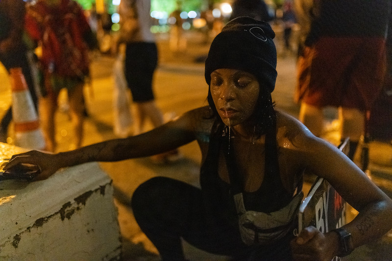 Shaynna Ford rests in an alley after having milk poured on her face after being pepper sprayed by police in Washington, DC on May 30, 2020.