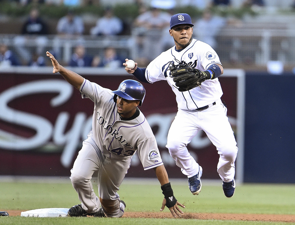 . SAN DIEGO, CA - SEPTEMBER 24:  Alexi Amarista #5 of the San Diego Padres jumps next to Rafael Ynoa #43 of the Colorado Rockies as he turns a double play during the first inning of a baseball game at Petco Park September, 24, 2014 in San Diego, California.  (Photo by Denis Poroy/Getty Images)