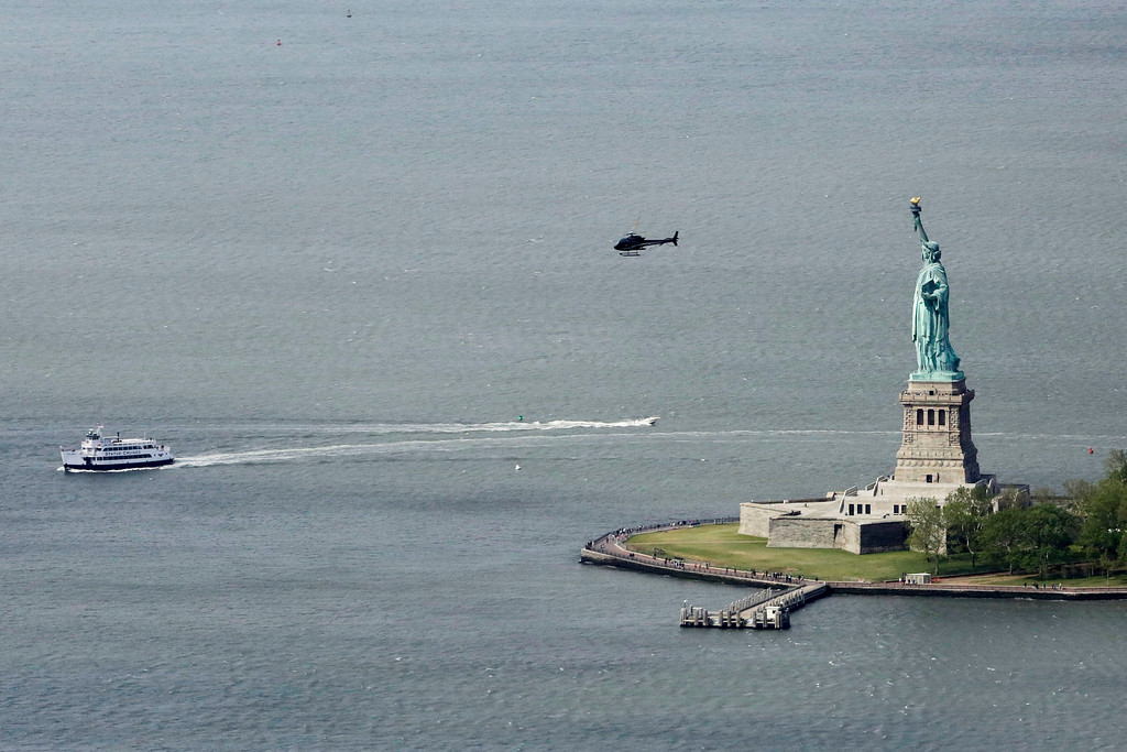 . A ferry and helicopter pass the Statue of Liberty in this view from the observatory at One World Trade Center, Wednesday, May 20, 2015, in New York.  (AP Photo/Mark Lennihan)