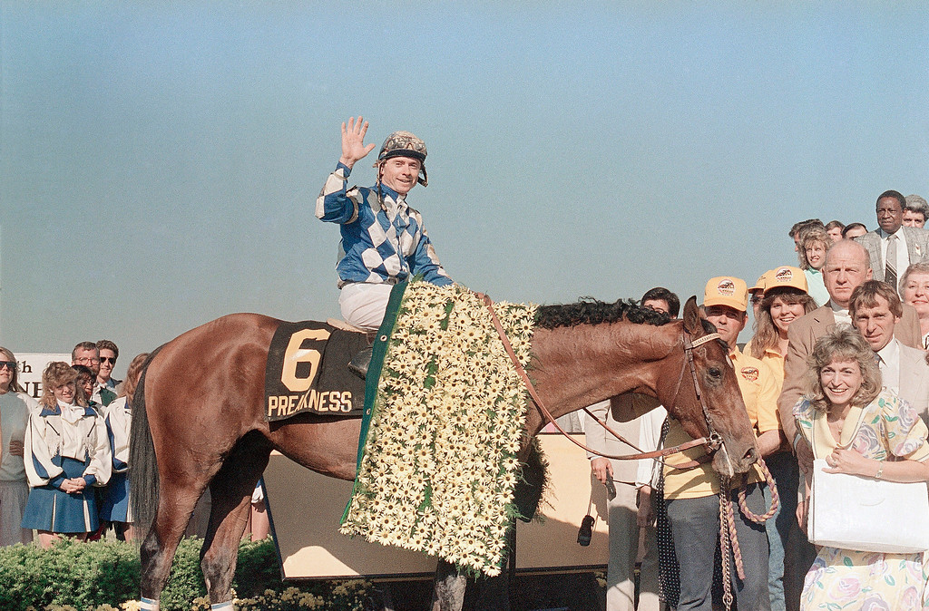 . Chris McCarron waves from atop of Alysheba in the victory circle, after winning the 112th running of the Preakness Stakes Pimlico Race Track on Saturday, May 16, 1987 in Baltimore. McCarron and Alysheba captured the second jewel in the Triple Crown series, but failed to win at Belmont, finishing fourth to Bet Twice. (AP Photo/Bill Smith)