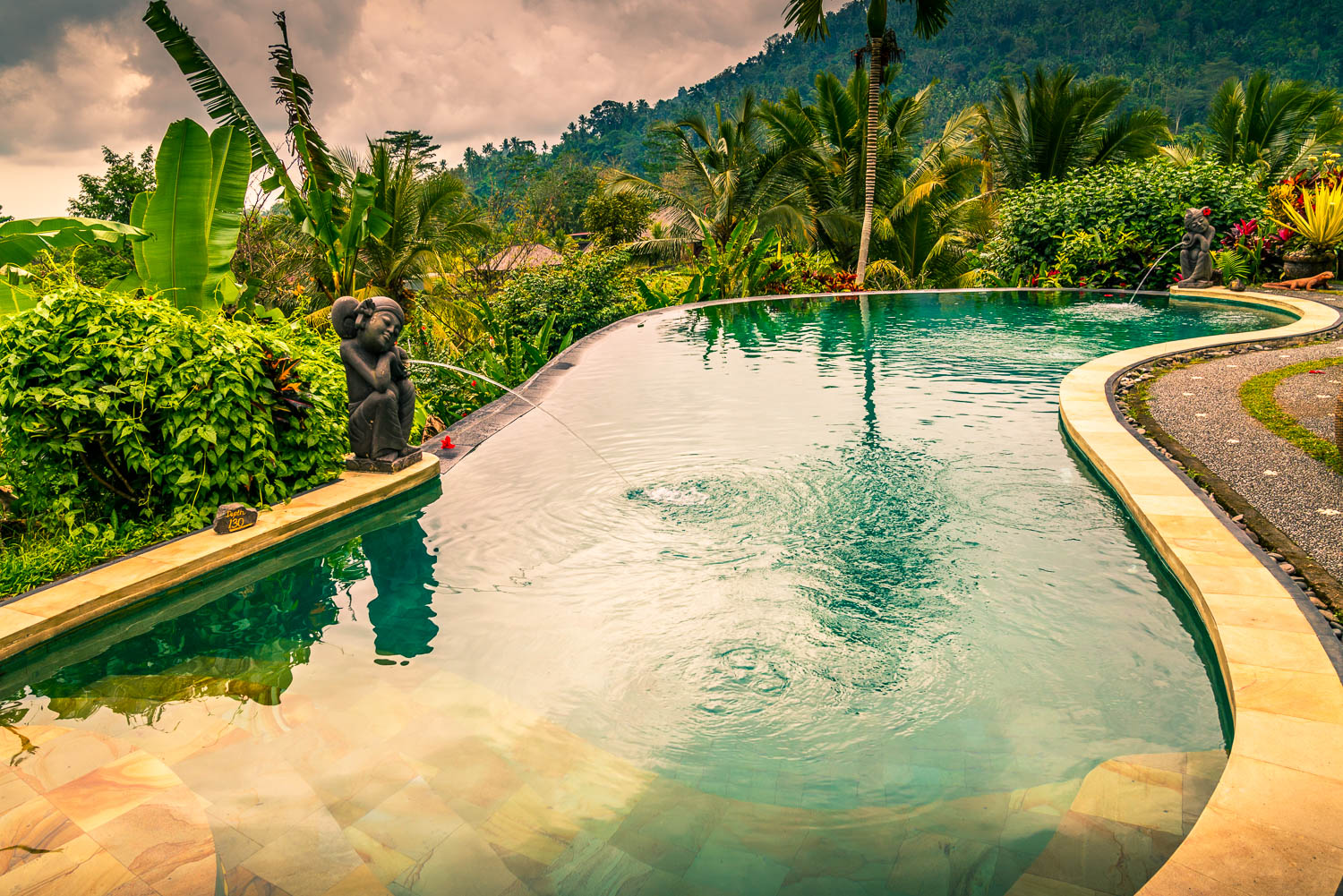 Sunset reflects in the pool at Suyra Shanti Villa. Beyond, emerald green .treetops and a deep green hill remind you that you're on the edge of a high hill.