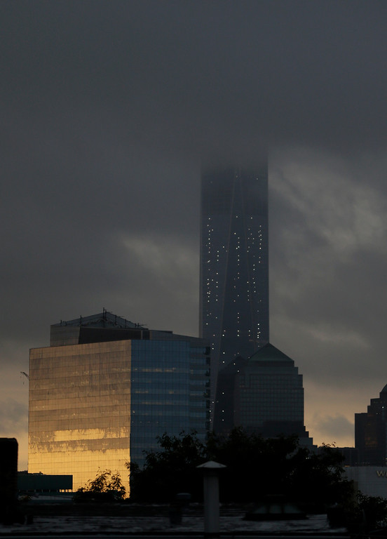 . Storm clouds obscure the top of 1 World Trade Center seen from The Heights neighborhood of Jersey City, N.J., at sunrise, Thursday, Sept. 11, 2014. Thirteen years after 9/11 forever changed the New York skyline, officials say developments at the World Trade Center are on track and on budget. (AP Photo/Julio Cortez)