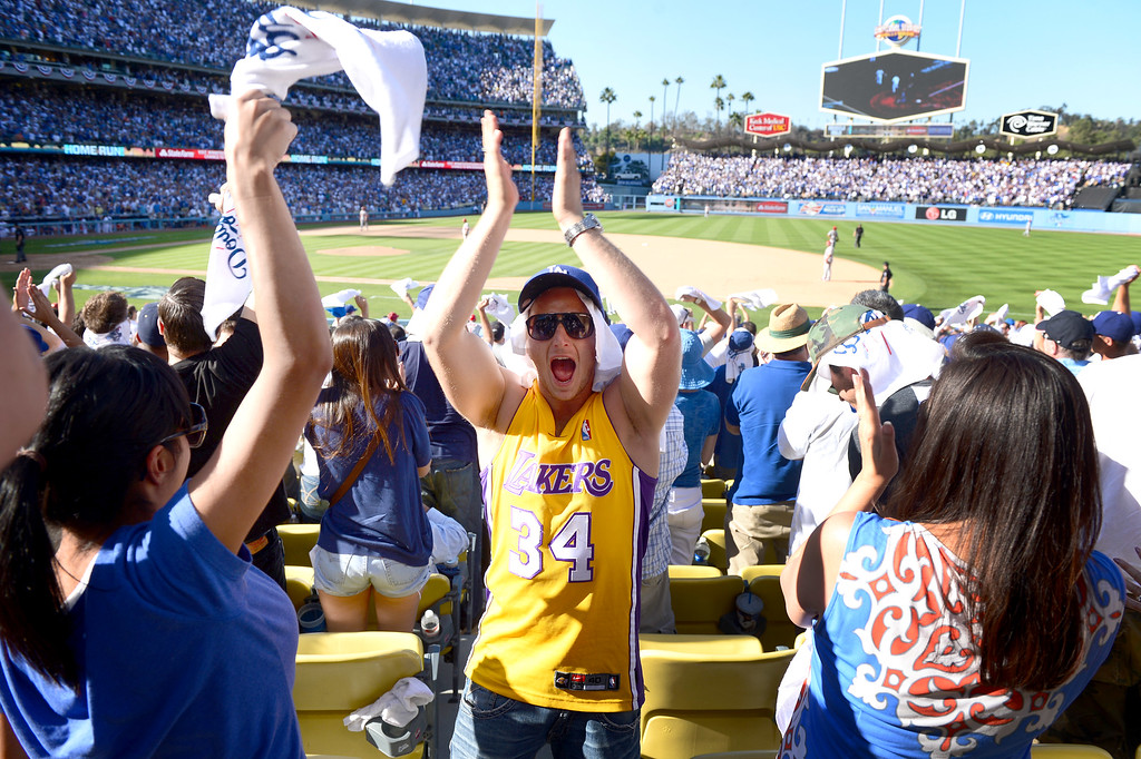 . Fans celebrate Los Angeles Dodgers\' A.J. Ellis\' home run to left field in the seventh during game 5 of the NLCS at Dodger Stadium Wednesday, October 16, 2013. (Photo by Sarah Reingewirtz/Los Angeles Daily News)